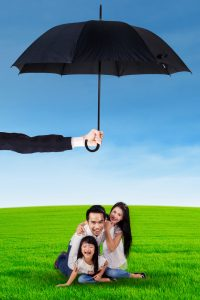 Family playing at field and protected by umbrella
